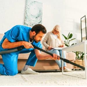 caregiver cleaning a carpet