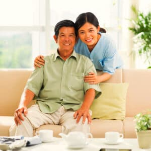 caregiver with elder man sitting on a couch