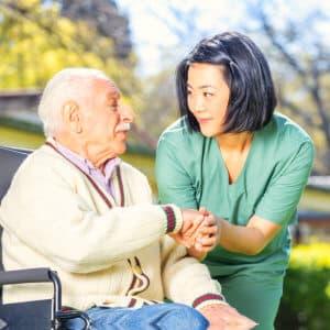 caregiver and elder man outdoors