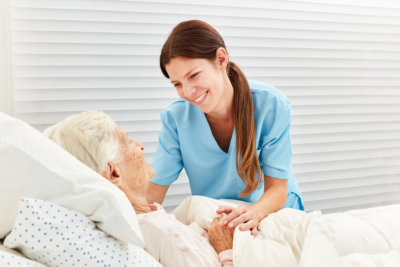 woman smiling at a senior in bed