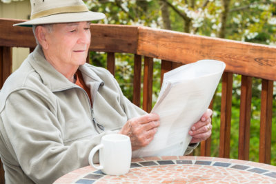 an elderly reading the news