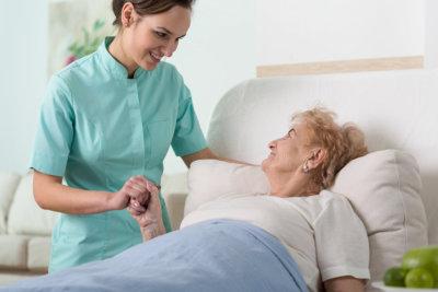 a nurse holding the hand of an elderly