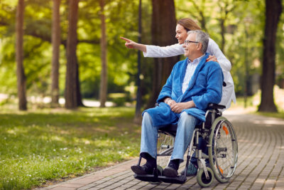 a caretaker and a man on a wheel chair in the park