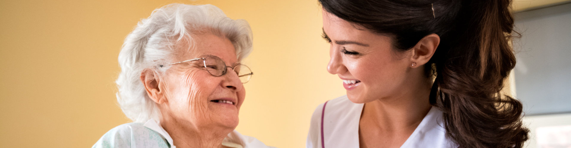an old lady and a nurse smiling at each other