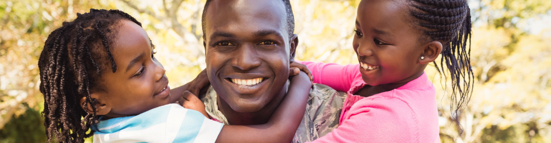 a veteran smiling with two kids