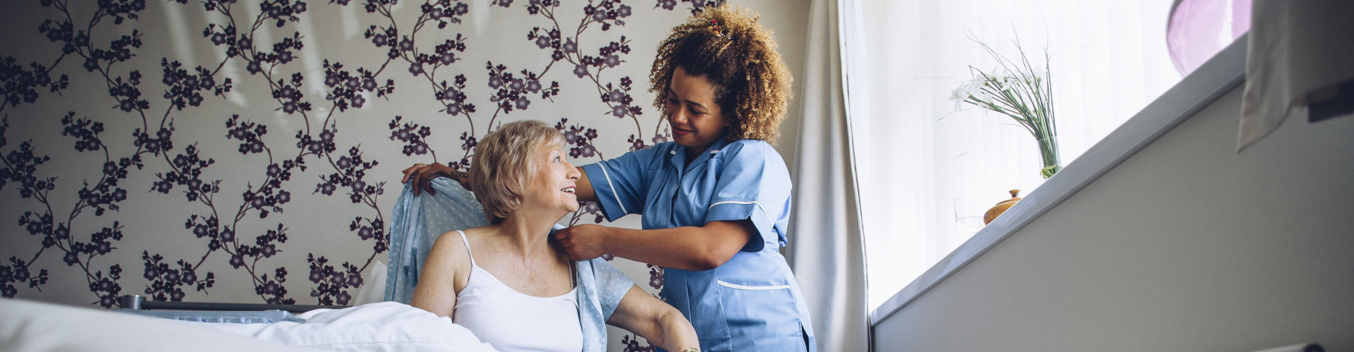 a nurse giving an old lady a blanket