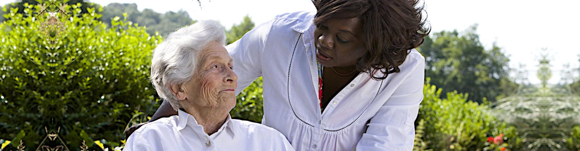 a senior on a wheel chair with a nurse