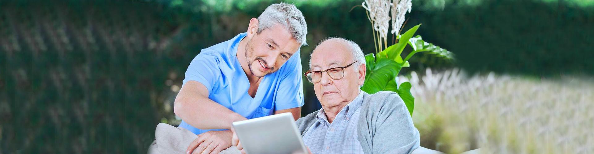 caregiver assisting elder man on using a tablet