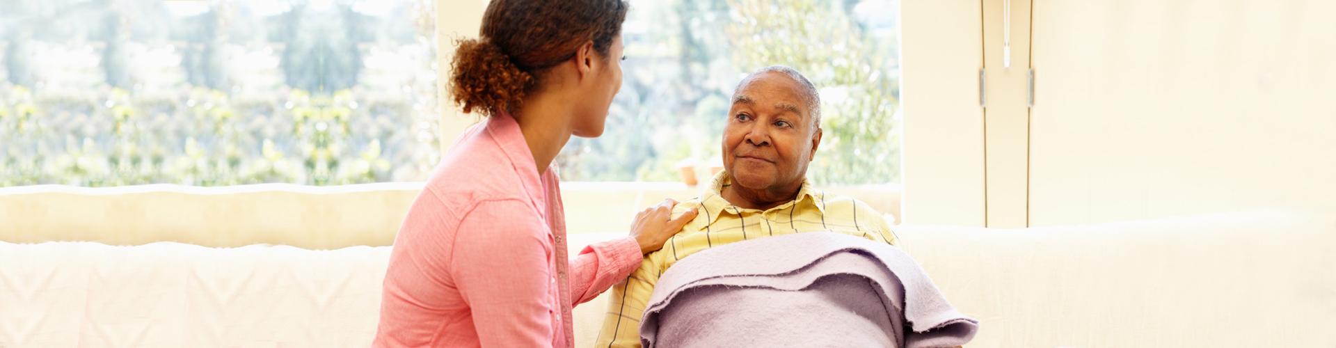 caregiver with elder man on bed